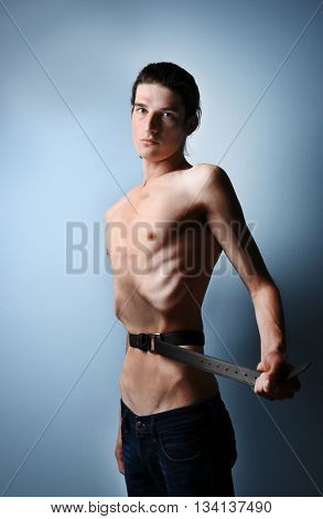 Skinny young man with anorexia tightening his waist with belt on grey background