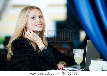 Young gorgeous European woman with pretty face thinking about something while sitting with laptop computer in cafe bar, dreamy beautiful female using portable net-book during work break in coffee shop