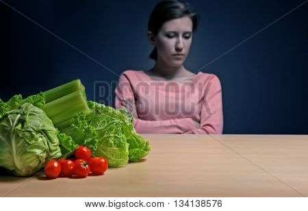 Desperate woman suffering from eating disorder on black background