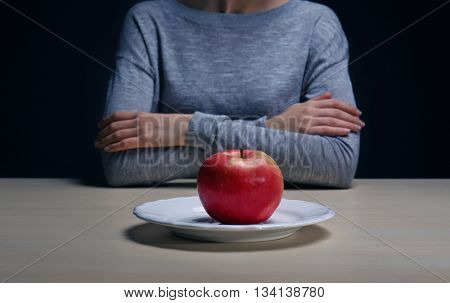 Desperate woman woman suffering from eating disorder on black background