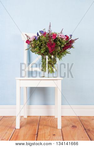 Mixed bouquet flowers in vase in blue interior