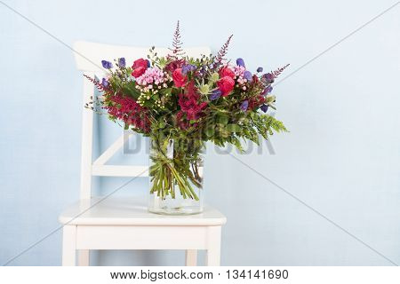 mixed bouquet flowers in vase on chair with blue background