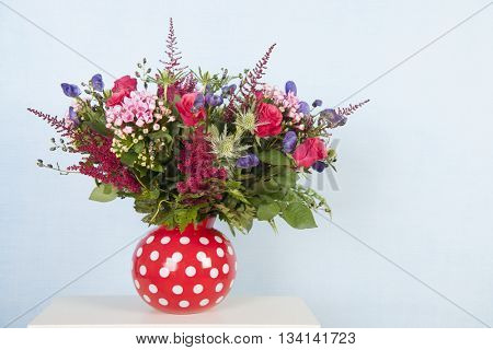 Red dotted vase with mixed bouquet flowers on blue background