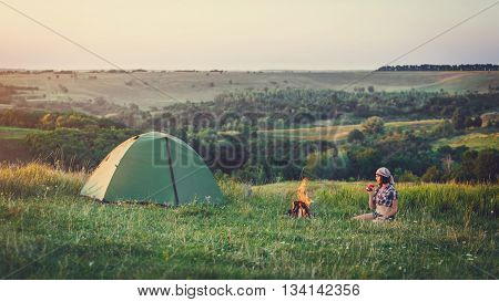 Girl near bonfire.Travel, tourism, camping - young slim sporty woman tourist  at the beautiful nature landscape sitting near the tent by the fire. Girl with drink in mug in her hands.
