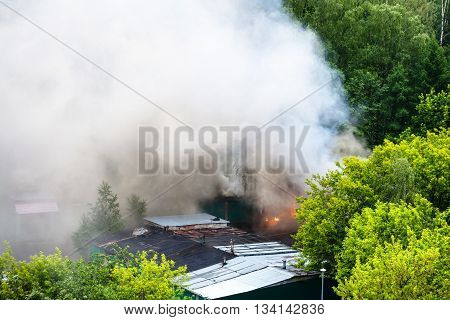 Wet Roofs, Burning Garage And White Smoke