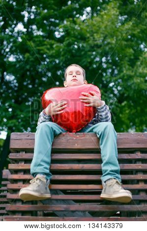boy closed his eyes hugging a big red heart. teenage love concept. the view from the bottom up