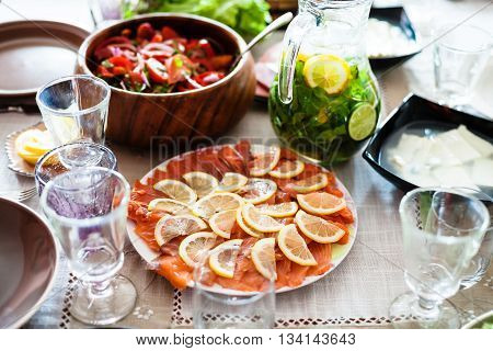 Plate With Sliced Salmon Fish And Salads On Table