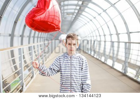 sad boy with a red heart in the hands. love-lorn. child standing with a red heart-shaped balloon. one-sided love