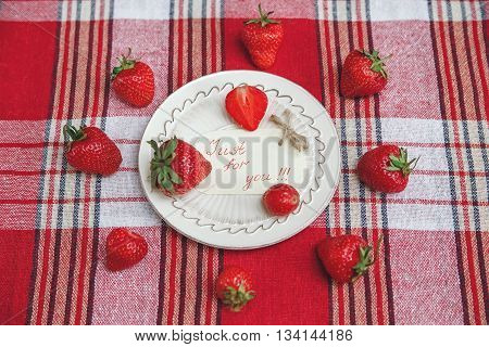 Red Fresh Strawberries on the Ceramic White Plate on the Check Tablecloth.Breakfast Organic Healthy Tasty Food.Wish Card.Cooking Vitamins Ingredients.Summer Fruits.