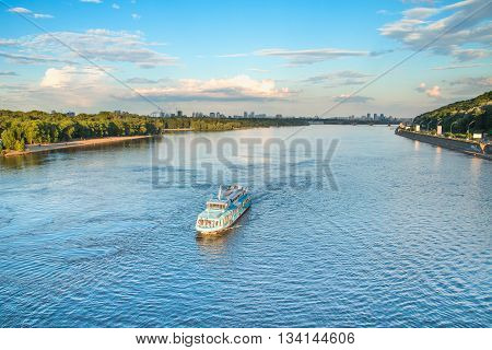 Tourist boat on the Dnepr River in Kiev, Ukraine, bridges and city skyline in background