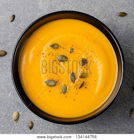 Pumpkin cream soup with pumpkin seeds in a black bowl. Grey stone background. Top view.