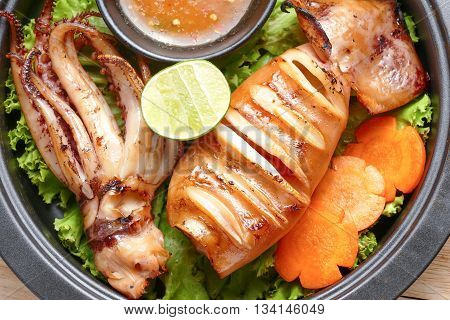Grilled Squid And Vegetable With Spicy Seafood Sauce On Frying Pan Over Wood Table