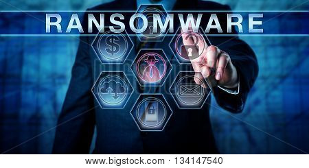 Male cybersecurity threat systems manager pushing RANSOMWARE on a transparent control interface. Computer crime concept for a hacking attack restricting file access to seek a ransom from a user.
