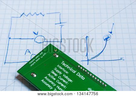 A notebook with some sketchs about electrical circuits, and a real electrical device (a sensor of humidity and temperature)