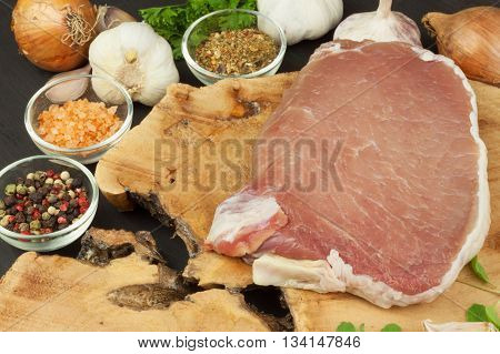Raw meat pork steak on a cutting board. Preparing barbecue pork steak. Sales of pork on the grill. Advertising on butcher. Raw pork butcher.