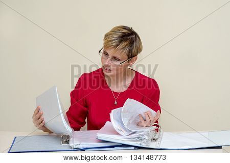 Business woman ina the red dress sitting at the table and carefully read the documents in the folder