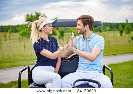It was great golfing with you. Smiling young golfing couple giving each other hi-five after satisfying round of golf, looking at each other