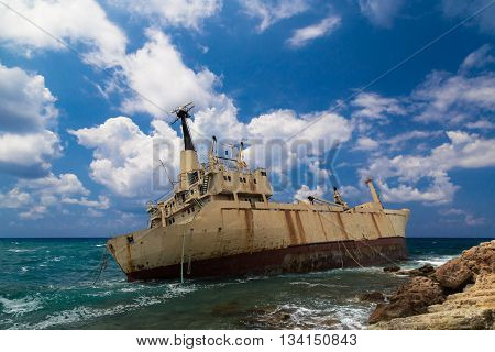 Seascape: boat shipwrecked near the rocky shore. Mediterranean near Paphos. Cyprus