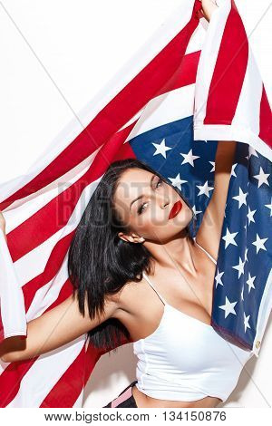 Sexy patriot brunette woman holding USA flag at white wall patriotism