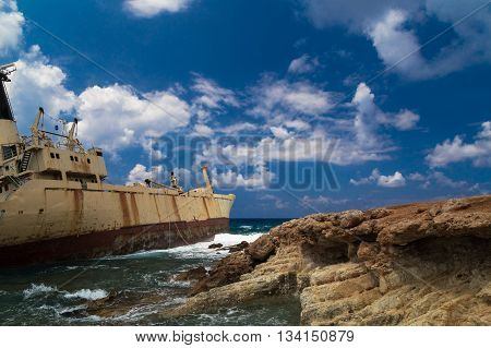 Shipwrecked boat near the rocky shore aground. Mediterranean Sea near Paphos. Cyprus