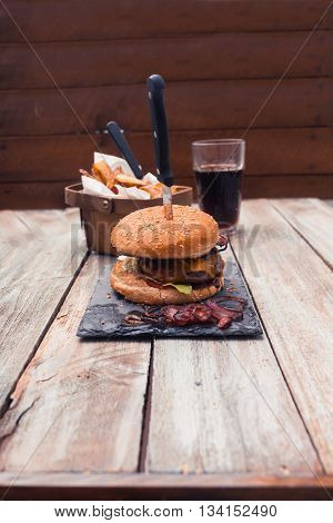 Bacon Cheese Burger, Potato Cuts And Coke On Table