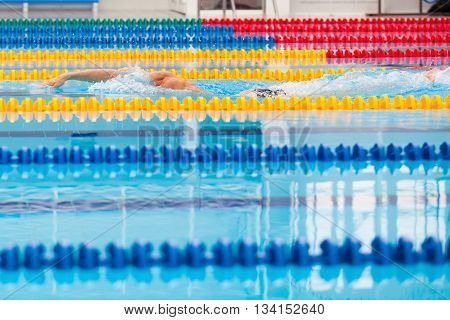 Man swimmer swimming crawl in blue water. Portrait of an athletic young male triathlete swimming crawl wearing a pink cap and swimming goggles while. Triathlete training for triathlon.