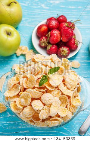 Bowl of cornflakes cereal on a blue wooden table and fresh strawberry apple behind.