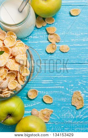 Bowl of cornflakes cereal on a blue wooden table and fresh apple milk behind. Vertical image with copy space.