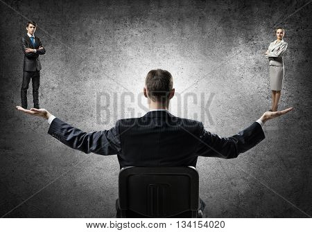 Businessman sitting in chair and holding in palms man and woman