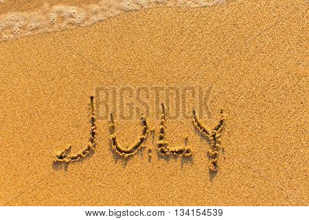 July - written on sandy beach with the soft wave.