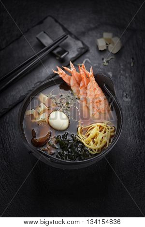 Japanese Cuisine. Shrimp Soup With Ramen Noodles Over Black Background.