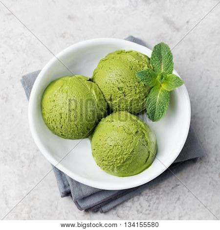 Green tea matcha ice cream scoop in white bowl on a grey stone background Copy space Top view