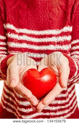 Hands of a young woman holding a red hart as symbol of love