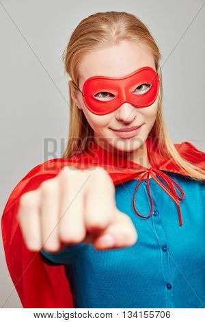 Strong woman dresses as a superhero for carnival Starke Frau als Superheld zu Karneval clenching her fist