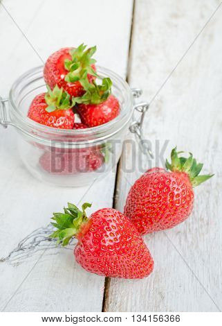 Red berry strawberry in glass jar on white rustic wooden background. Background from freshly harvested strawberries. Strawberry background. Selective focus. Shallow depth of field. Vertical.
