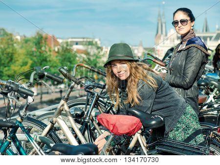 Two women locking their bikes at big cycling parking in Amsterdam, Dutch capital