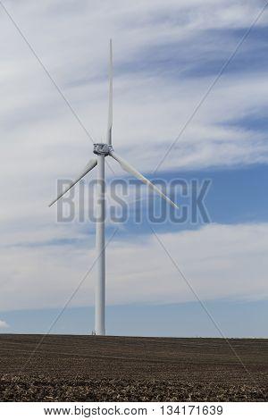 A wind turbine in a rural plowed field.