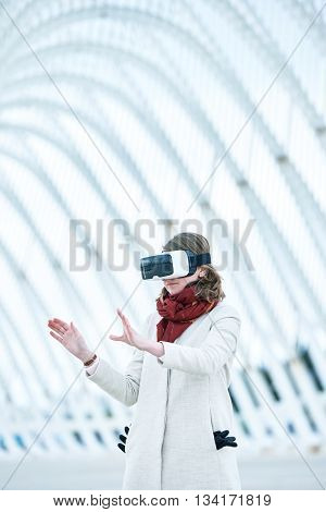 Woman Wearing A Virtual Reality Headset, Controlling The Experience With Hand Gesture