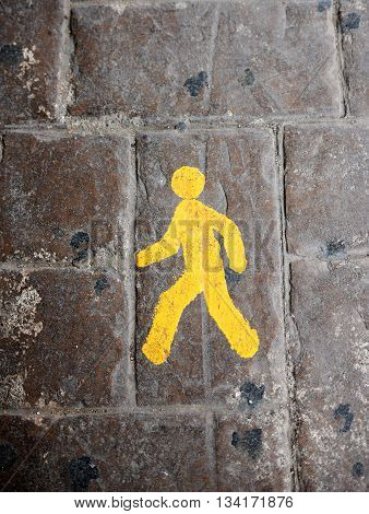 Yellow pedestrian lane sign on a cobblestone road