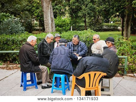 Athens Greece - March 27 2016: Old friends playing cards and laughing in National Garden parkthe center of the Greek capital Athens behind the Greek Parliament building