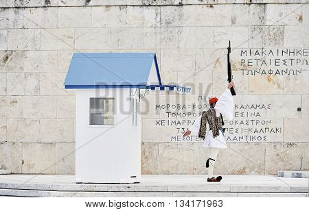 Rear view of honor Evzones guard with raised rifle in front of the Tomb of the Unknown Soldier at the Parliament Building in Syntagma Square Athens Greece.