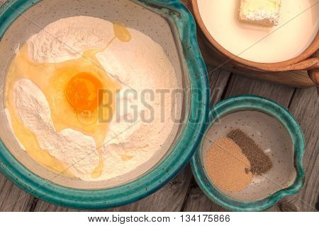 Number 1 of bread making series.  Four cups of flour and egg in a bowl, three fourths of a teaspoon of cardamom spice and one packet of yeast in another bowl, and four tablespoons of butter with one cup of milk and three fourths of a cup of sugar in a pot