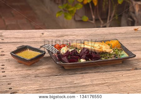 Summer salad with micro greens, feta cheese, tomatoes, red and yellow beets, and chicken with a cilantro salad dressing on a rustic wood picnic table.