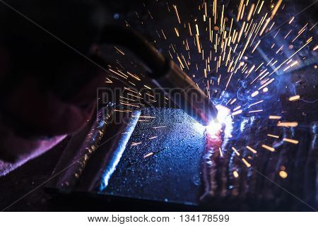 The welding spark light in close-up scenethe torch of welding machine with the spark light in blue.Close-up of the sparking light of the welding process.Sparking light from the welding process.