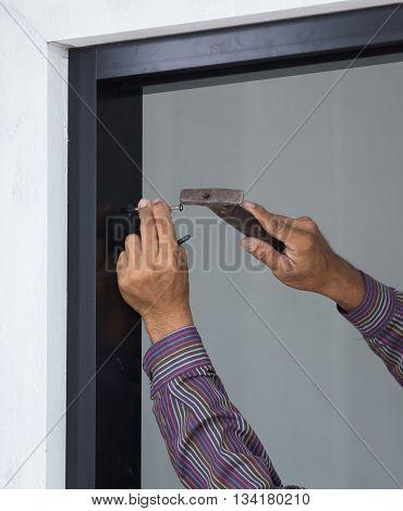 Worker Hammering Nail Into Aluminium Framework