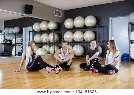 Friends Sitting Together On Hardwood Floor In Gym