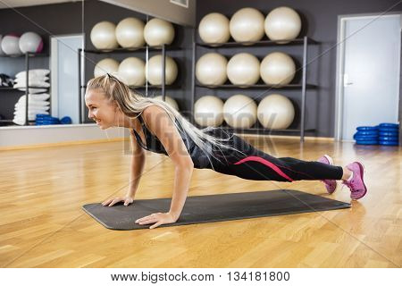 Woman Doing Pushups On Mat In Gym