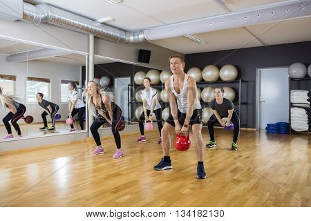 Male And Female Friends Lifting Kettlebells In Gym