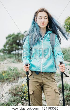 Beautiful hiker young woman with trekking poles walking in summer outdoor