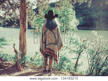 Fashionable young woman wearing in hat and poncho standing on coast in the forest and looking at lake rear view